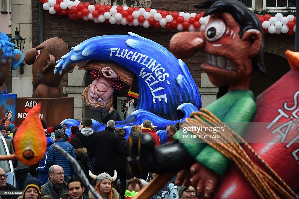 A carnival float depicting German Chancellor Angela Merkel in a small boat on a wave of refugees stands in front of the city hall in Duesseldorf, western Germany, after the Rose Monday (Rosenmontag) street parade has been cancelled on February 8, 2016. Traditional Rose Monday carnival parades in several western German cities have been cancelled due to stormy weather. / AFP / PATRIK STOLLARZ