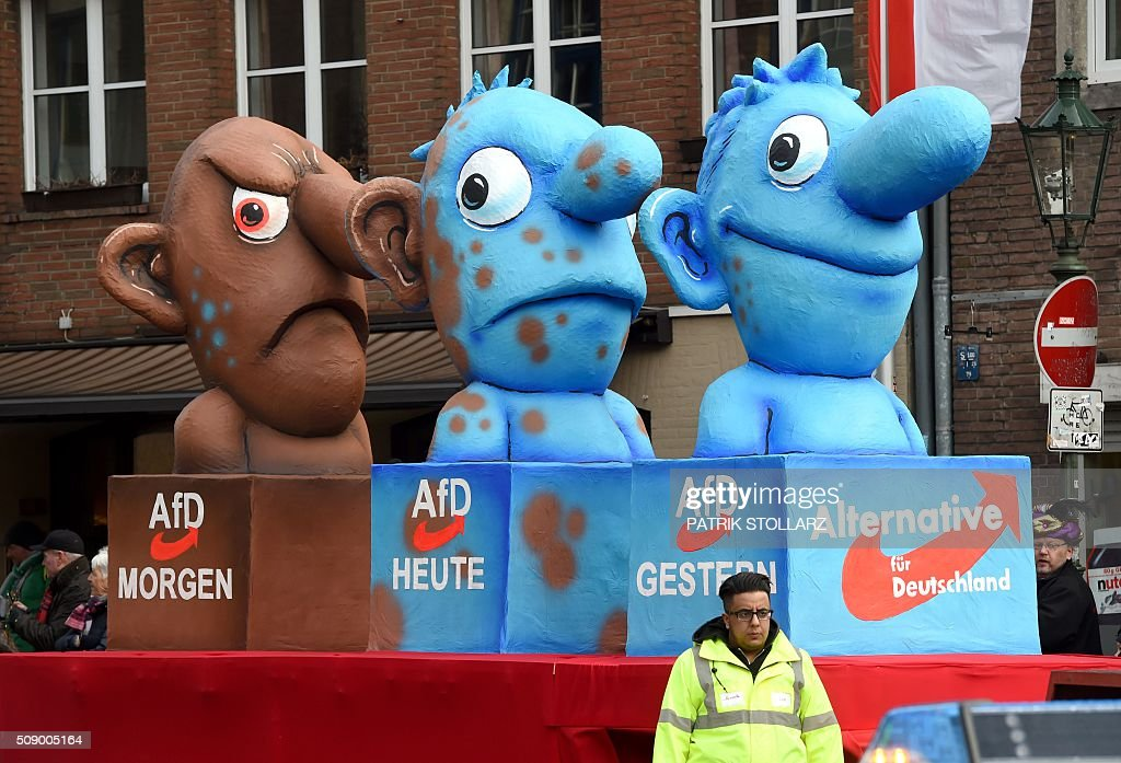 A carnival float, depicting Germany's eurosceptic right-wing populist AfD party metamorphosing from a blue to a brown character, stands in front of the city hall in Duesseldorf, western Germany, after the Rose Monday (Rosenmontag) street parade has been cancelled on February 8, 2016. Traditional Rose Monday carnival parades in several western German cities have been cancelled due to stormy weather. / AFP / PATRIK STOLLARZ