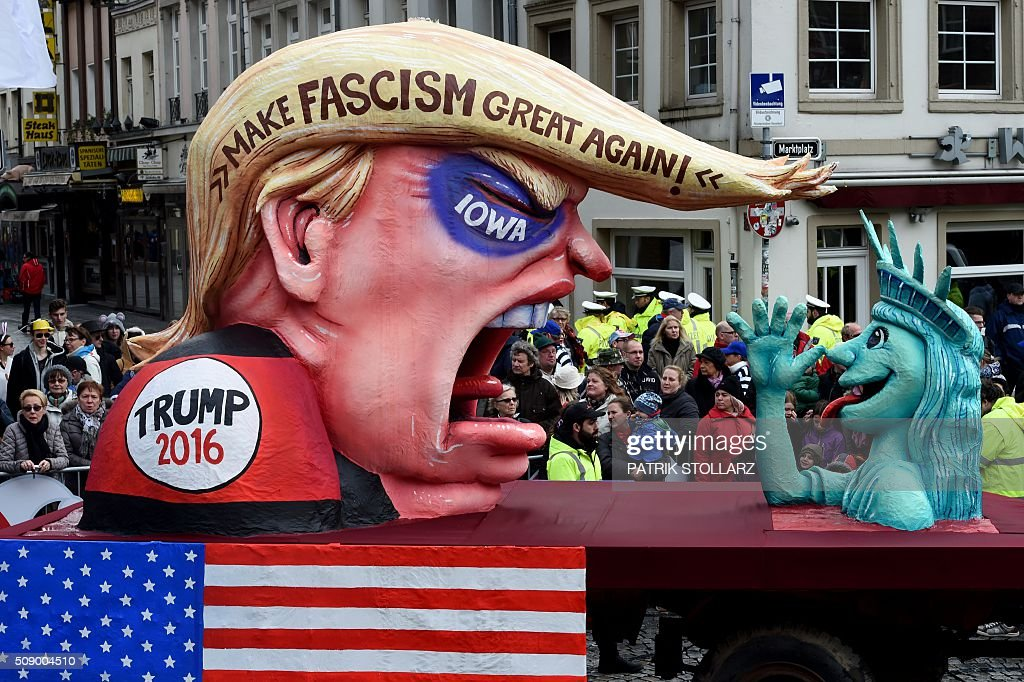 A carnival float depicting Republican presidential candidate Donald Trump (L) and the Statue of Liberty stands in front of the city hall in Duesseldorf, western Germany, after the Rose Monday (Rosenmontag) street parade has been cancelled on February 8, 2016. Traditional Rose Monday carnival parades in several western German cities have been cancelled due to stormy weather. / AFP / PATRIK STOLLARZ