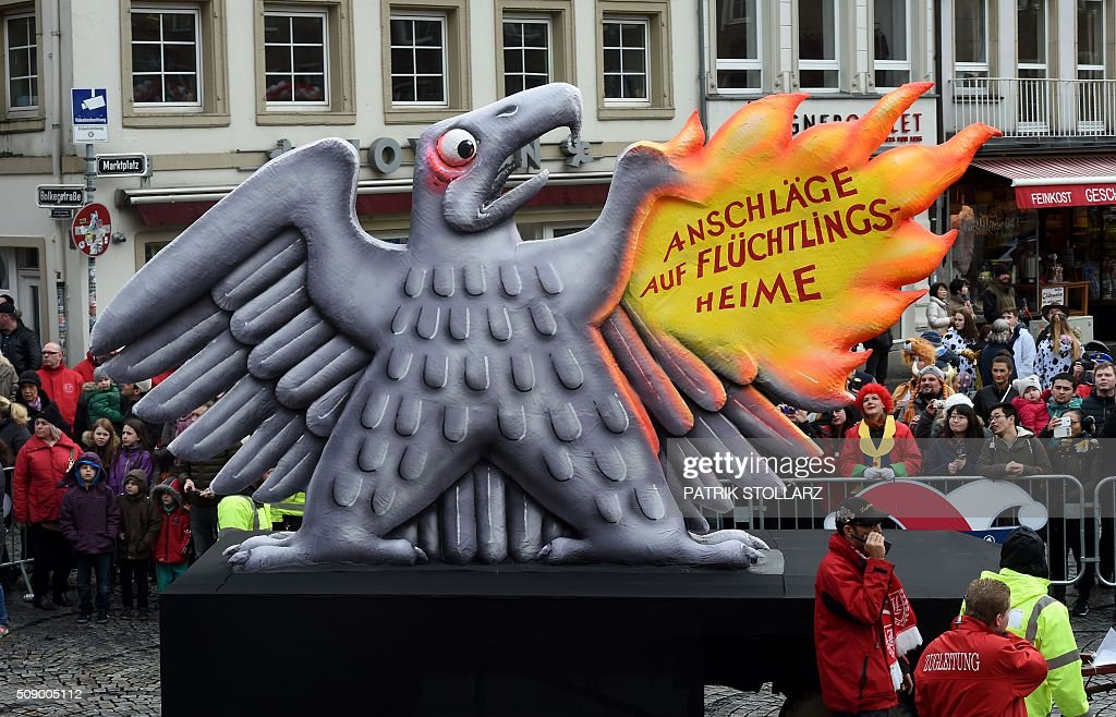A carnival float, depicting the German federal eagle getting frightened as one of its wings burns due to attacks on refugee shelters, stands in front of the city hall in Duesseldorf, western Germany, after the Rose Monday (Rosenmontag) street parade has been cancelled on February 8, 2016. Traditional Rose Monday carnival parades in several western German cities have been cancelled due to stormy weather. / AFP / PATRIK STOLLARZ