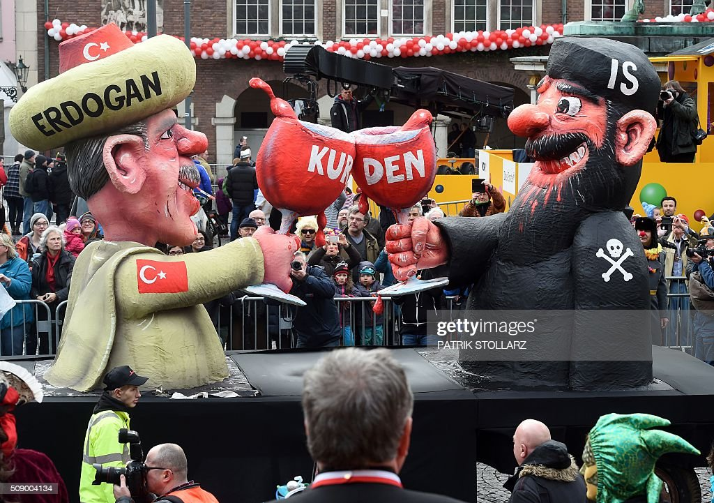A carnival float depicting Turkish President Recep Tayyip Erdogan (L) clinking his glass with a fighter of the Islamic State (IS) stands in front of the city hall in Duesseldorf, western Germany, after the Rose Monday (Rosenmontag) street parade has been cancelled on February 8, 2016. Traditional Rose Monday carnival parades in several western German cities have been cancelled due to stormy weather. / AFP / PATRIK STOLLARZ