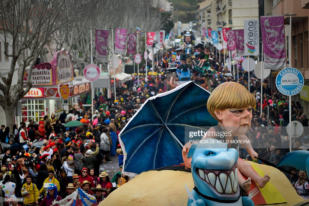 A carnival float with a figure representing German Chanceller Angela Merkel is towed during the annual parade in Torres Vedras on February 9, 2016. The Torres Vedras Carnival is allegedly the 'most Portuguese' of all the carnivals in the country recognized by the strong political and football satire of the revelers disguises and their floats. / AFP / PATRICIA DE MELO MOREIRA