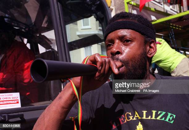 A carnival goer blows a horn at the Notting Hill Carnival 2000 in London