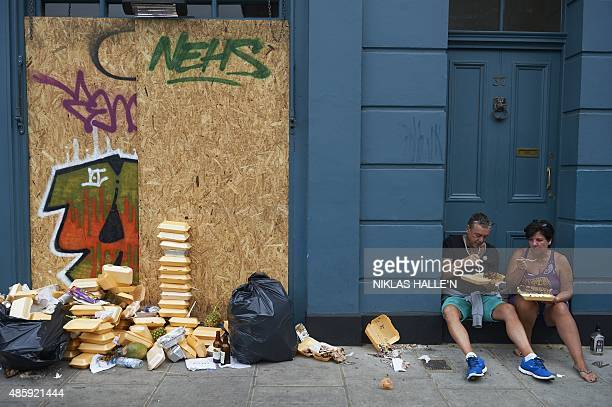 Carnival goers sits and eat food in a doorway near a pile of rubbish on the first day of the Notting Hill Carnival in west London on August 30 2015...