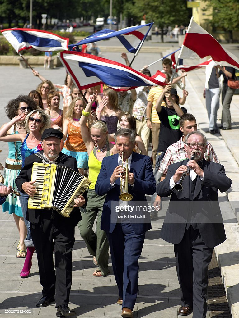 Carnival procession led by three senior male musicians : Stock Photo