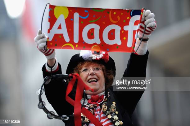 A carnival reveler accompanies a float in the Rose Monday parade on February 20 2012 in Cologne Germany Rose Monday is the highpoint of the Carnival...