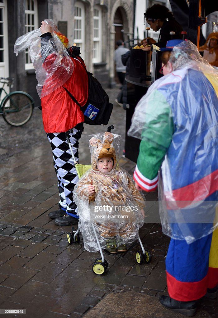 A Carnival reveller protects himself from rain during a carnival parade called 'Schull- un Veedelszoech' as part of the carnival season on February 7, 2016 in Cologne, Germany. Carnival partying and parades, a centuries-old tradition in western and southwestern Germany, traditionally occurs in February and runs until Ash Wednesday, the start of Lent, and culminates in Rose Monday parades and festivities. Police are on added alert this year, particularly in Cologne, due to the New Year`s Eve sex attacks on women that have been attributed to gangs of North African men, predominantly from Algeria and Morocco.