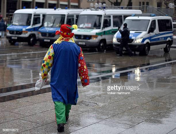 Carnival reveller walks in front of Policevans during 'Weiberfastnacht' celebrations as part of the carnival season on February 4 2016 in Cologne...