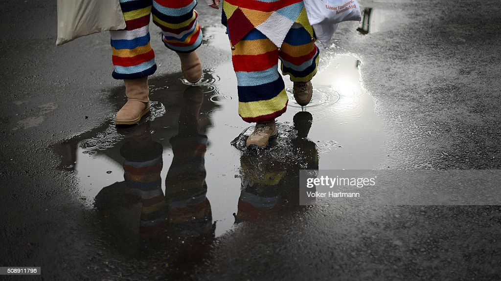 Carnival revellers walk through a puddle during a carnival parade called 'Schull- un Veedelszoech' as part of the carnival season on February 7, 2016 in Cologne, Germany. Carnival partying and parades, a centuries-old tradition in western and southwestern Germany, traditionally occurs in February and runs until Ash Wednesday, the start of Lent, and culminates in Rose Monday parades and festivities. Police are on added alert this year, particularly in Cologne, due to the New Year`s Eve sex attacks on women that have been attributed to gangs of North African men, predominantly from Algeria and Morocco.