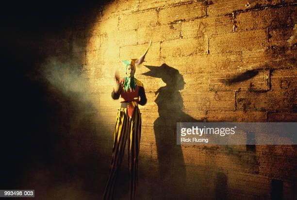Carnival tallman juggling by wall, shadow against wall