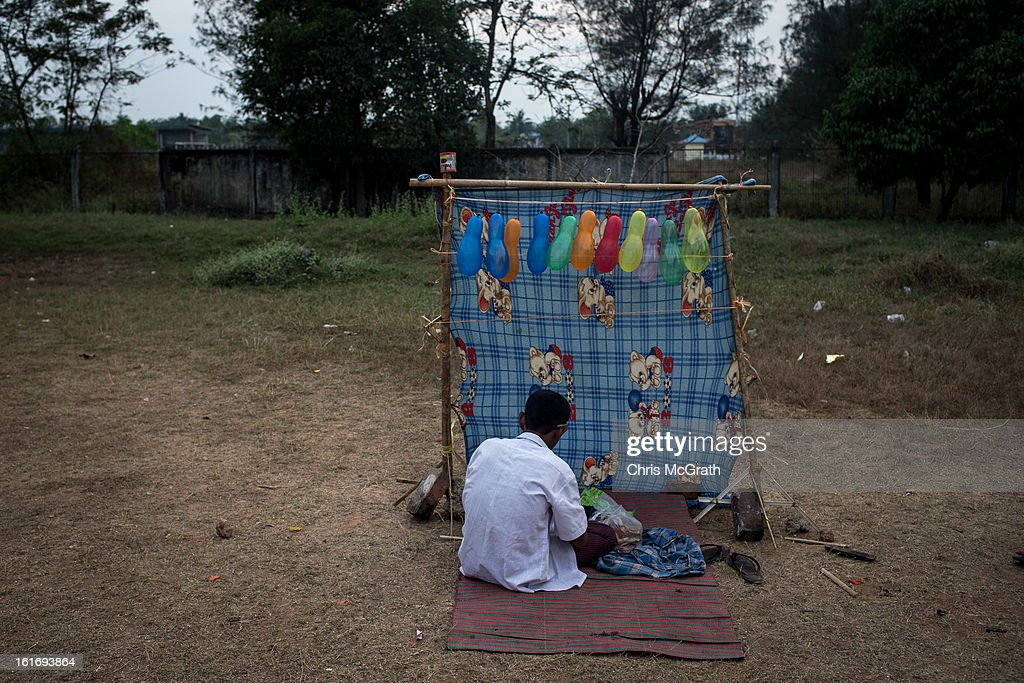 A carnival worker prepares a rubber band, balloon popping stand, prior to the start of the rural carnival in South Dagon Township on February 14, 2013 in Yangon, Burma. Myanmar is going through rapid political and economic reforms initiated by the countries first civilian president Thein Sein after years of military junta rule.