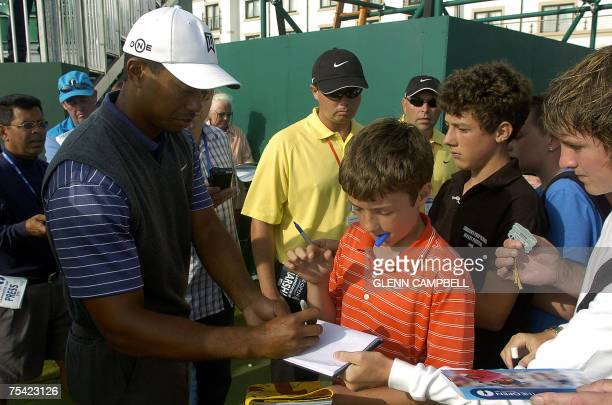 Tiger Woods from the USA signs autographs for the young golf fans after his practice round for the 136th Open Golf Championship in Carnoustie...