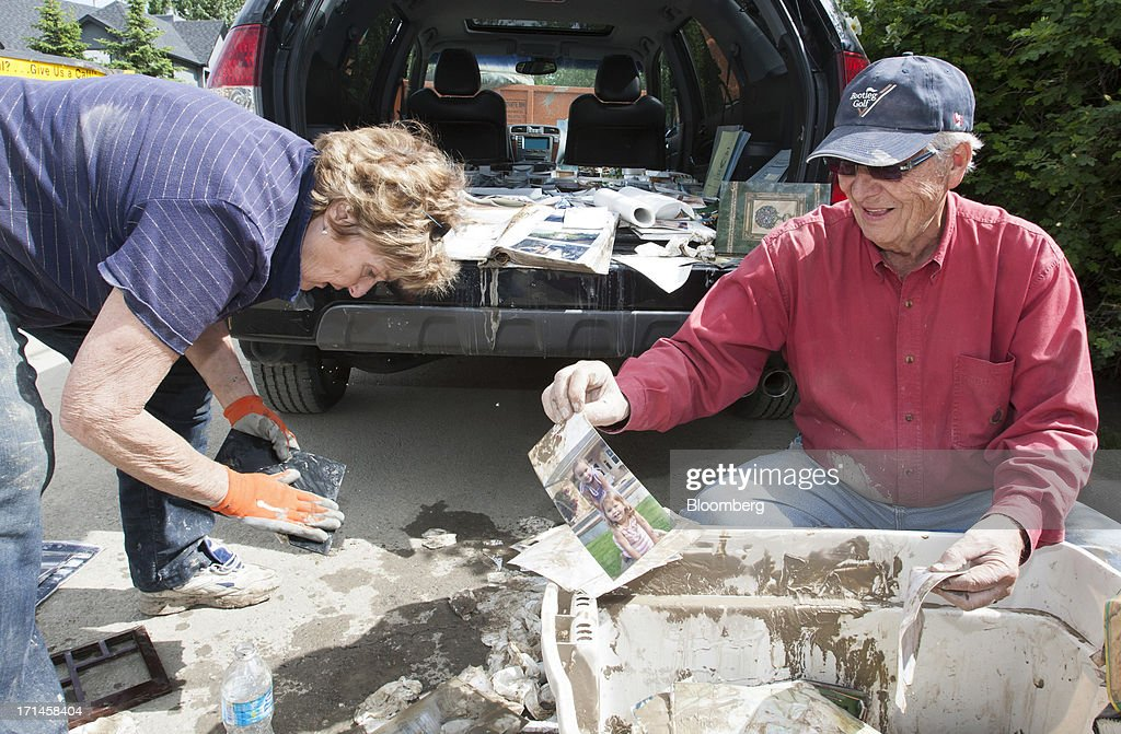Carol Armstrong, left, and Don Armstrong sort through water-damaged photographs as they help clean their son's home in Rideau Park after flooding in Calgary, Alberta, Canada, on Monday, June 24, 2013. Water levels in Calgary subsided and crews are working to restore power as officials confirmed a fourth fatality in the worst flood in Alberta's history. Photographer: Keith Morison/Bloomberg via Getty Images