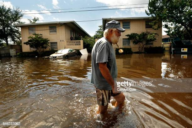 Carol Orr wades through kneedeep waters after Hurricane Irma to check on his 82yearold father Bernard Orr who lives by the river on September 12 2017...