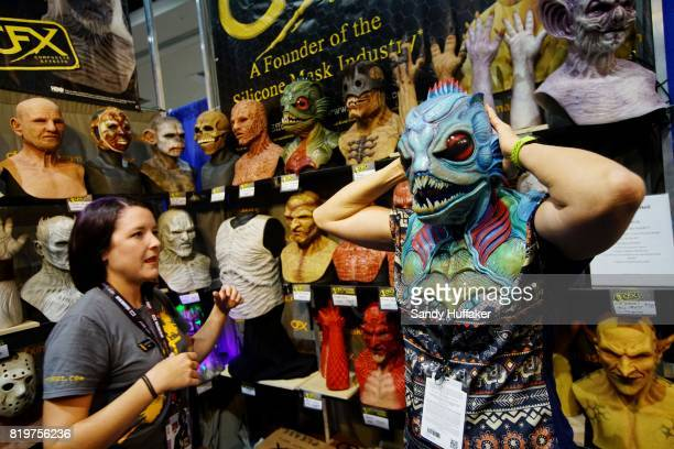 Carol Smith tries on a rubber mask at the CFX Composite Effects booth at Comic Con International on July 20 2017 in San Diego California Comic Con...