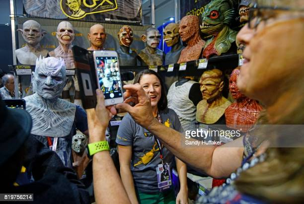 Carol SmithL tries on a rubber mask at the CFX Composite Effects booth at Comic Con International on July 20 2017 in San Diego California Comic Con...