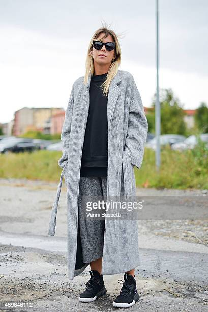 Carola Bernard poses wearing a Grifoni coat and Adidas shoes before the Gucci show during the Milan Fashion Week Spring/Summer 16 on September 23...