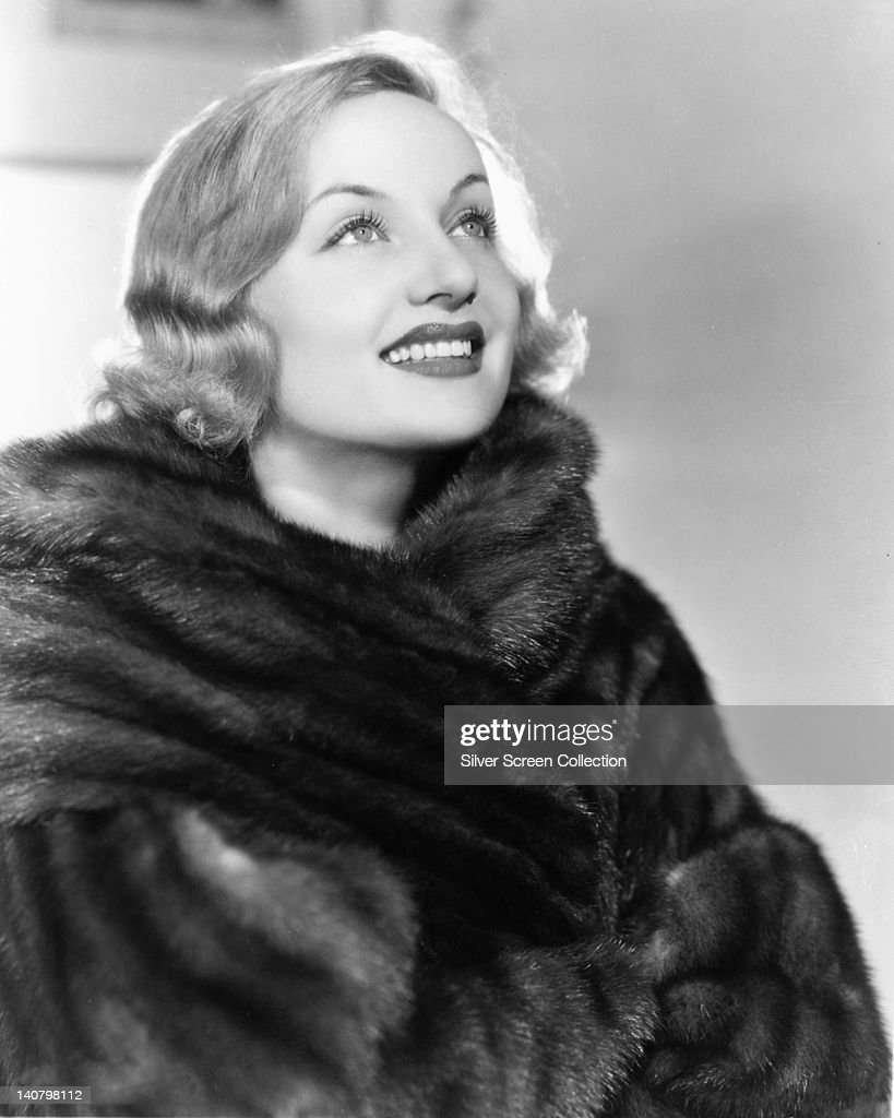 <a gi-track='captionPersonalityLinkClicked' href=/galleries/search?phrase=Carole+Lombard&family=editorial&specificpeople=93207 ng-click='$event.stopPropagation()'>Carole Lombard</a> (1908-1942), US actress, smiling while wearing a fur coat in a studio portrait, against a white background, circa 1935.