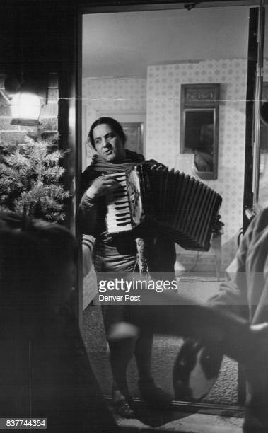 Carolers singing Mexican Christmas songs are accompanied on the accordion by Mrs Juanita Dominguez of 3246 Quitman St where Monday night's 'Los...