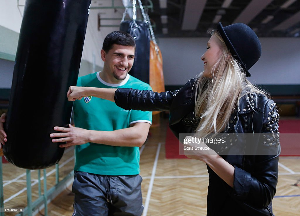 Carolin Niemczyk (R) of the pop band Glasperlenspiel tries to box the punchbag of WBO Cruiserweight champion <a gi-track='captionPersonalityLinkClicked' href=/galleries/search?phrase=Marco+Huck&family=editorial&specificpeople=2264905 ng-click='$event.stopPropagation()'>Marco Huck</a> (L) of Germany in the ring of his training camp on Usedom on September 4, 2013 in Zinnowitz, Germany.