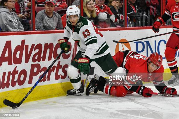 Carolina Hurricanes Center Victor Rask hold onto the leg of Minnesota Wild Right Wing Tyler Ennis during a game between the Minnesota Wild and the...