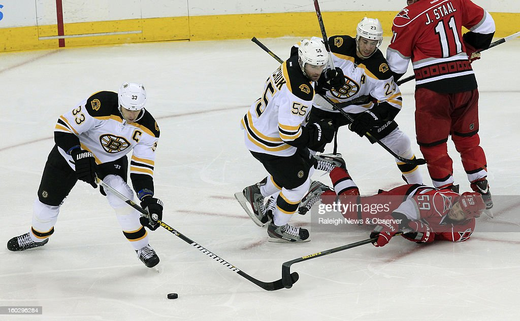 Carolina Hurricanes' Chad LaRose (59) battles Boston Bruins' Zdeno Chara (33), Johnny Boychuk (55) and Chris Kelly (23) for the puck during the second period at PNC Arena in Raleigh, North Carolina, Monday, January 28, 2013.