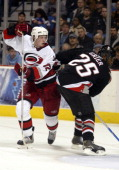 Carolina Hurricanes' Eric Staal avoids a check by Mike Greer of the Buffalo Sabres during a game against the Buffalo Sabres at the HSBC Arena in...