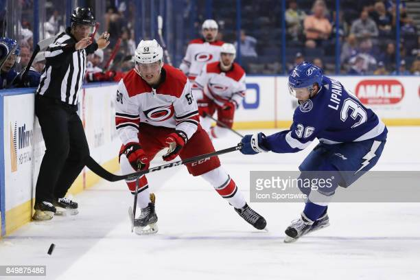 Carolina Hurricanes forward Janne Kuokkanen and Tampa Bay Lightning center Alexei Lipanov battle for the puck in the 3rd period of the NHL preseason...