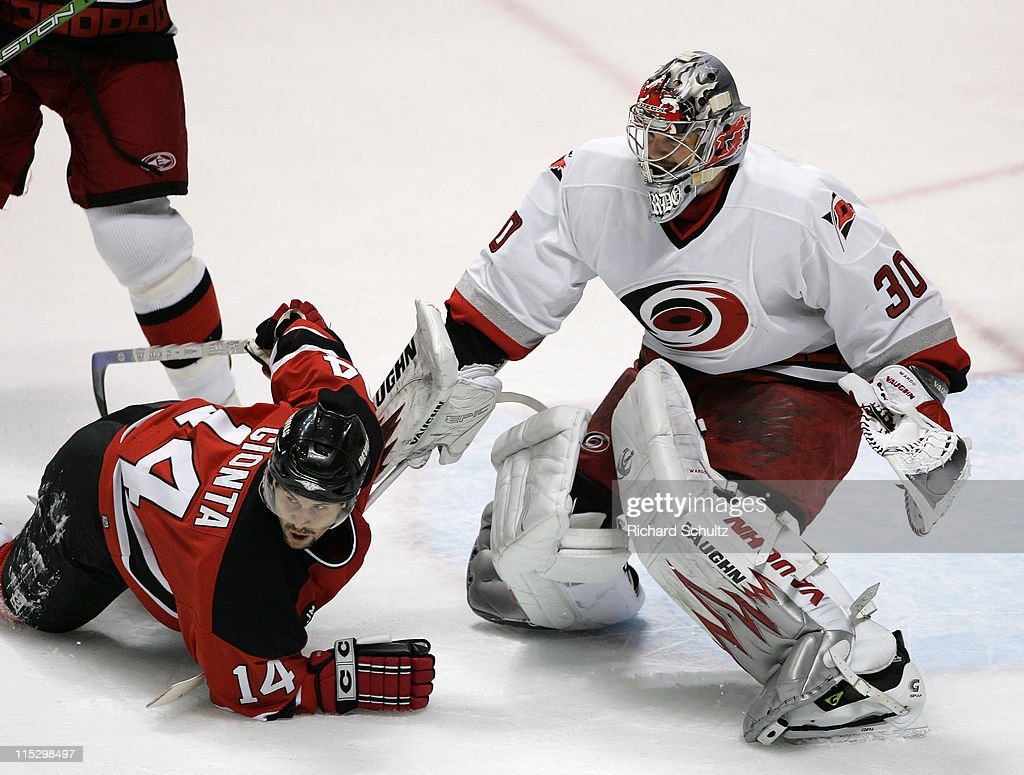 Carolina Hurricanes' goaltender Cam Ward keeps his eye on the puck as <a gi-track='captionPersonalityLinkClicked' href=/galleries/search?phrase=Brian+Gionta&family=editorial&specificpeople=202116 ng-click='$event.stopPropagation()'>Brian Gionta</a> #14 of the New Jersey Devils goes down in front of the crease during the third period of game three in the Eastern Conference Semifinals of the Stanley Cup Playoffs at the Continental Airlines Arena in East Rutherford, NJ on Wednesday, May 10, 2006. Carolina defeated the Devils 3-2 and take a 3-0 lead in the series.