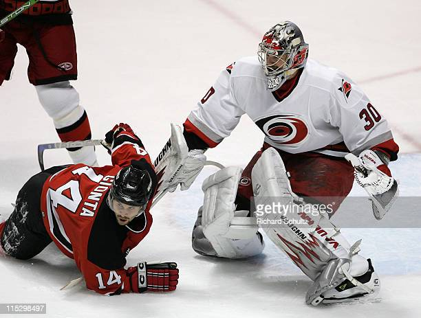 Carolina Hurricanes' goaltender Cam Ward keeps his eye on the puck as Brian Gionta of the New Jersey Devils goes down in front of the crease during...