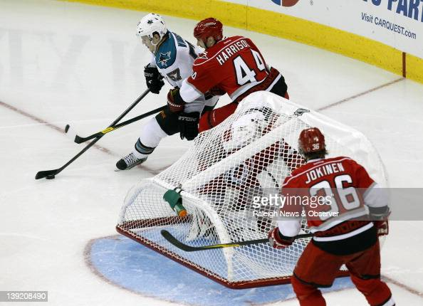 Carolina Hurricanes goaltender Justin Peters is trapped under a dislodged net as teammates Jay Harrison and Jussi Jokinen defend the San Jose Sharks'...