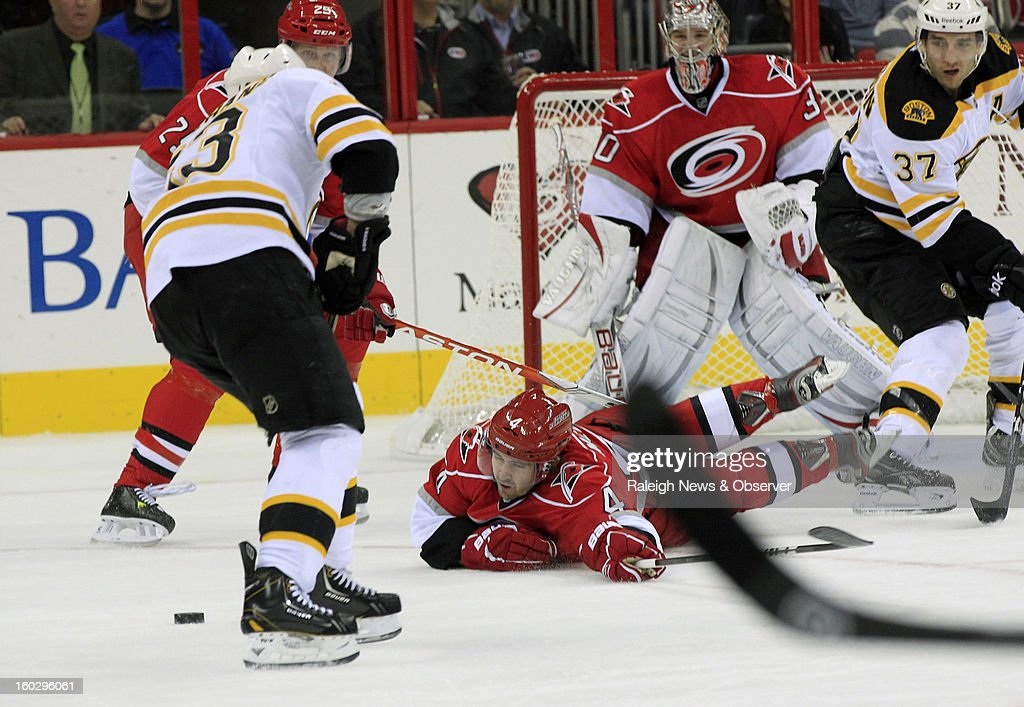 Carolina Hurricanes' Jamie McBain (4) tries to stop Boston Bruins' Brad Marchand (63) during the first period of an NHL game at PNC Arena in Raleigh, North Carolina, Monday, January 28, 2013.