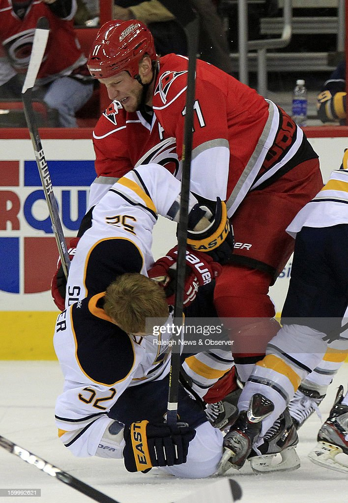 Carolina Hurricanes' Jordan Staal (11) slams Buffalo Sabres' Alexander Sulzer (52) to the ice during the first period of an NHL game at PNC Arena in Raleigh, North Carolina, Thursday, January 24, 2013.