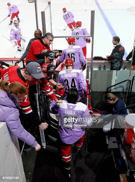 Carolina Hurricanes players enter the ice for pregame warm up on Hockey Fights Cancer night prior to an NHL game against the New York Islanders on...