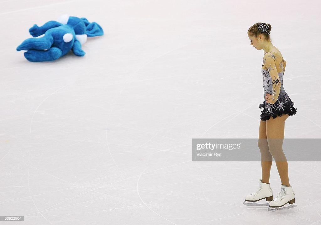 Carolina Kostner of Italy skates over to a gift thrown onto the ice by a fan after she performed in the women's Free Skating program of figure...
