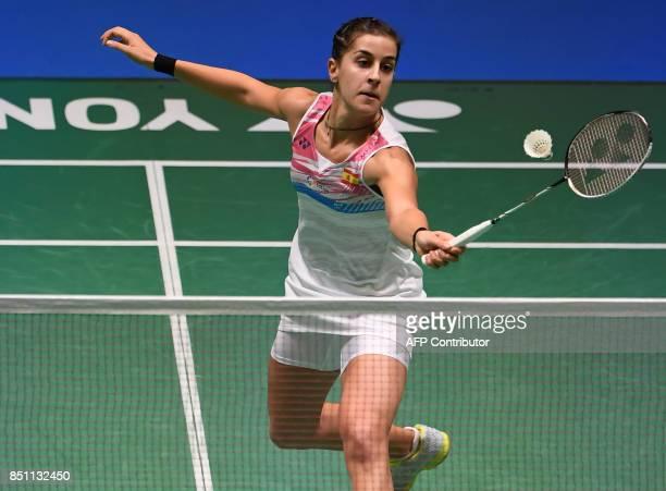Carolina Marin of Spain hits a return towards Akane Yamaguchi of Japan during the women's singles quarterfinal match at the Japan Open Badmintons...