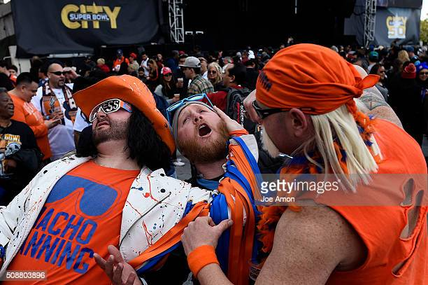 Carolina Panther fan Tommy West 29 of Folsom CA poses with Macho Manning and Bronco Hulkster at the Denver Broncos fan rally in Super Bowl City...