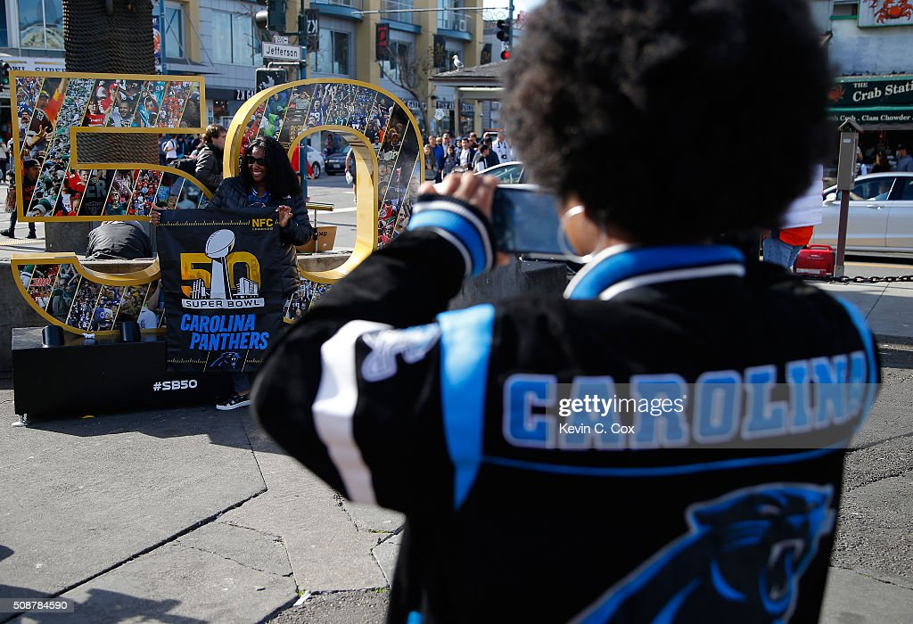 A Carolina Panthers fan takes a picture for another fan in front of a Super Bowl 50 sign at Fisherman's Wharf on February 6, 2016 in San Francisco, California.