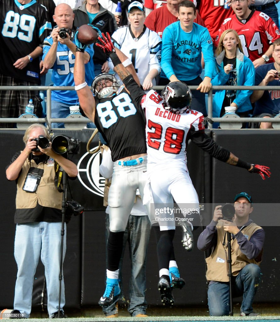 Carolina Panthers' Greg Olsen (88) reaches up to grab a touchdown pass over Atlanta Falcons' Thomas DeCoud (28) in the first half at Bank of America Stadium on Sunday, December 9, 2012, in Charlotte, North Carolina.