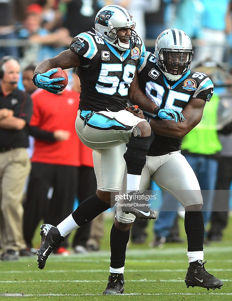 Carolina Panthers linebacker Thomas Davis (58) celebrates his interception against the Atlanta Falcons with teammate defensive end Charles Johnson (95) during fourth-quarter action at Bank of America Stadium on Sunday, December 9, 2012, in Charlotte, North Carolina.