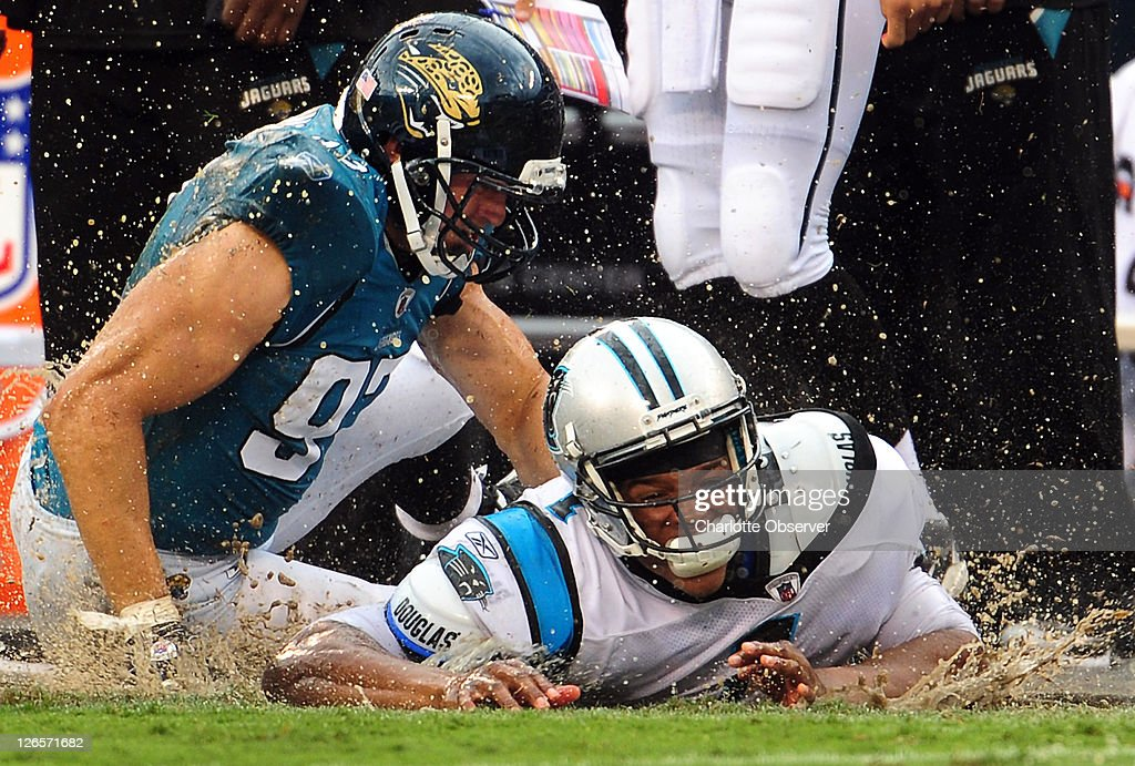 Carolina Panthers quarterback Cam Newton (1) kicks up water from the saturated field after being tackled by Jacksonville Jaguars defenders John Chick (97) and Nate Collins (98), following a pass during fourth-quarter at Bank of America Stadium in Charlotte, North Carolina, Sunday, September 25, 2011. The Panthers defeated the Jaguars 16-10.
