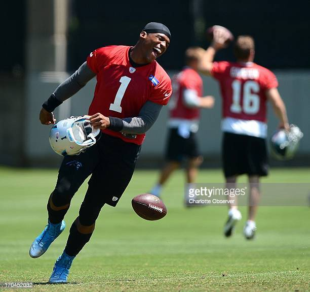 Carolina Panthers quarterback Cam Newton laughs after failing to catch a ball thrown to him during minicamp practice Thursday June 13 in Charlotte...