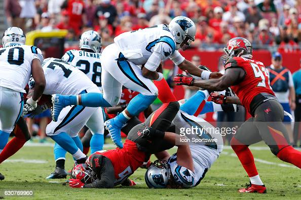 Carolina Panthers quarterback Cam Newton leaps over Tampa Bay Buccaneers defensive end Cliff Matthews and into the arm of Tampa Bay Buccaneers...