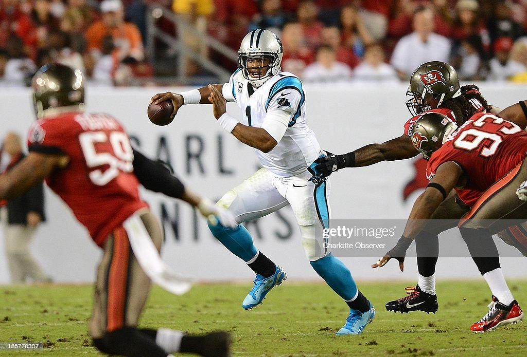Carolina Panthers quarterback Cam Newton (1) scrambles away from the Tampa Bay Buccaneers' defense for yardage in the second quarter at Raymond James Stadium in Tampa, Florida, on Thursday, October 24, 2013.