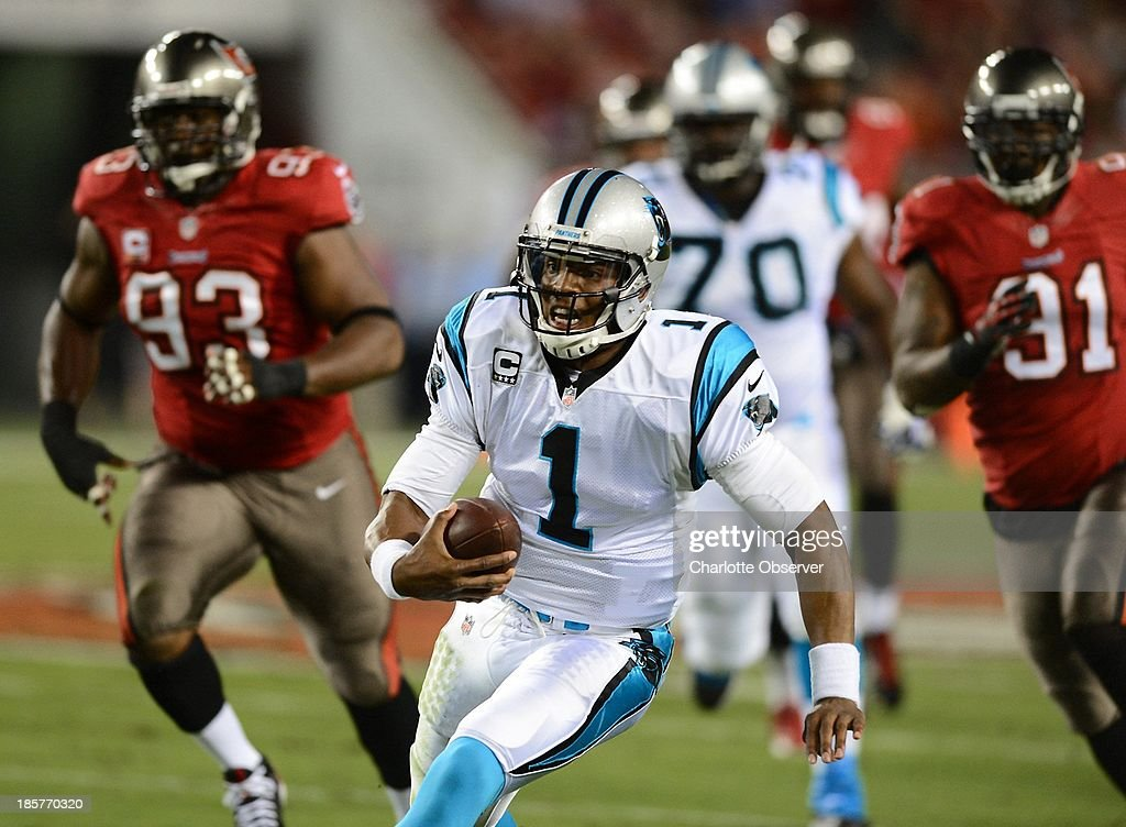 Carolina Panthers quarterback Cam Newton (1) scrambles for a first down as the Tampa Bay Buccaneers defense chases during the first quarter at Raymond James Stadium in Tampa, Florida, on Thursday, October 24, 2013.