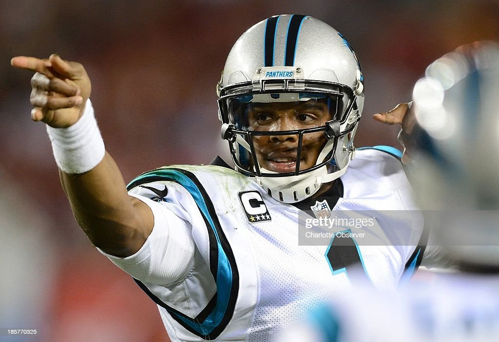 Carolina Panthers quarterback Cam Newton signals a first down after scrambling away from the Tampa Bay Buccaneers defense for the necessary yardage in the first quarter at Raymond James Stadium in Tampa, Florida, on Thursday, October 24, 2013.