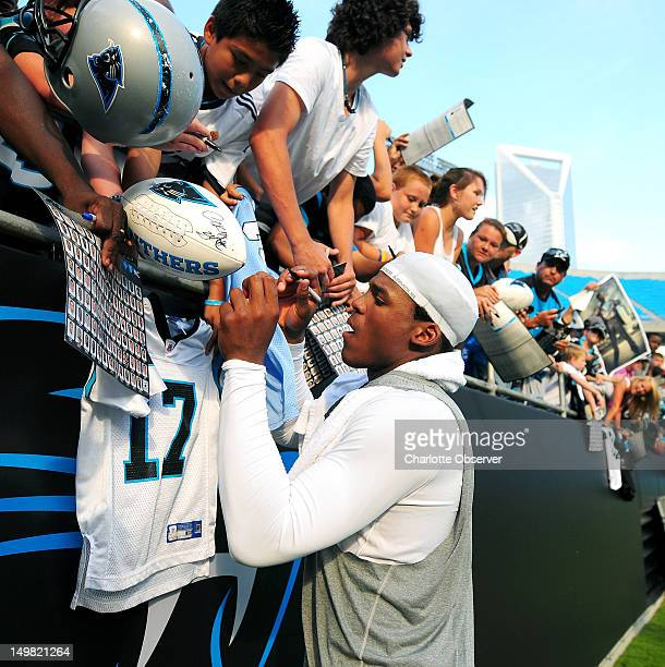 Carolina Panthers quarterback Cam Newton signs autographs for fans during Fan Fest at Bank of America Stadium on Saturday August 4 2012