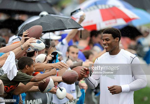 Carolina Panthers quarterback Cam Newton stops to sign autographs for fans following practice on Tuesday July 31 2012 at Wofford College in...