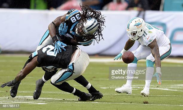 Carolina Panthers' Robert Lester and Drayton Florence collide after deflecting a pass intended for Miami Dolphins' Mike Wallace during the first half...