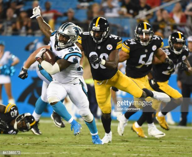 Carolina Panthers running back Cameron ArtisPayne evades Pittsburgh Steelers defensive back Greg Ducre during a NFL preseason game between the...